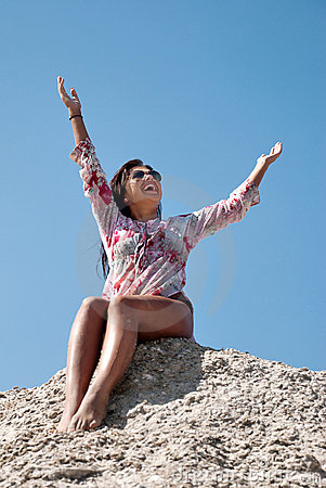 Young woman stretches her hand towards the sky