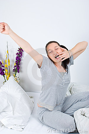 Young woman stretching and yawning