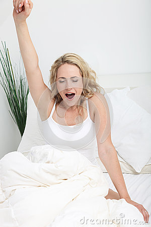 Young woman stretching and yawning in bed