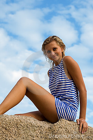 Young woman in striped vest sits on a rock