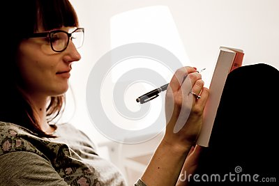 A young woman studying at home sitting on bed and taking notes in a book.