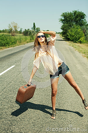 Young woman with suitcase hitchhiking along a road