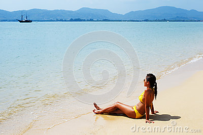 Young woman sun bathing on a sandy beach of Thailand