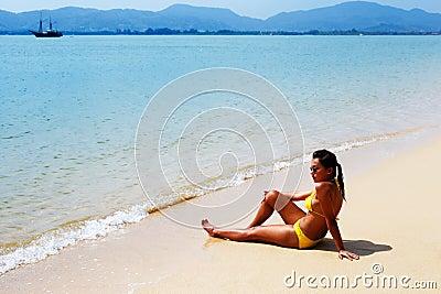 Young woman sun bathing on a sandy beach of Thailand