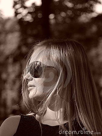 Young woman with sun glasses in sepia