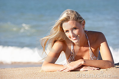 Young Woman Sunbathing On Beach