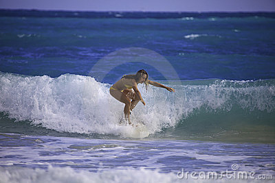 Young woman surfing in hawaii
