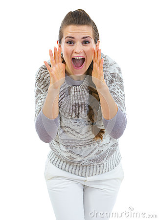 Young woman in sweater shouting through megaphone shaped hands