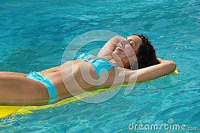 Young woman swimming on mattress