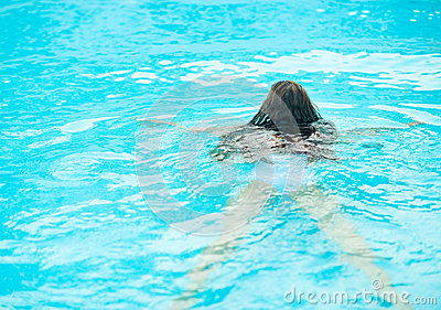 Young woman swimming in pool. Rear view