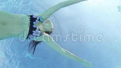 Young woman swimming underwater. Looking up at a young woman swimming stock video footage