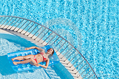 Young woman in swimsuit bakes lying on inflatable mattress