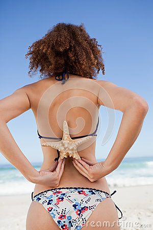 Young woman in swimsuit holding a starfish