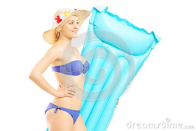 Young woman in swimsuit holding a swimming mattress