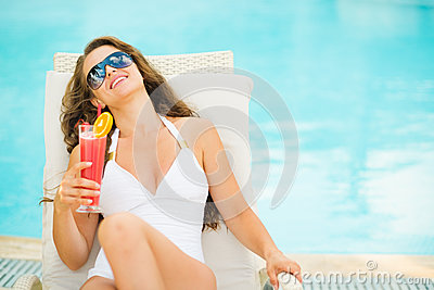 Young woman in swimsuit relaxing with cocktail