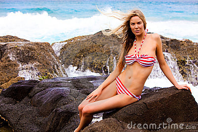 Young Woman in Swimsuit Sitting on Rocks on the Be