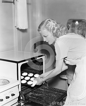 Free Young Woman Taking Cookies Out Of  An Oven Royalty Free Stock Photo - 52016885
