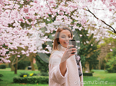 Young woman taking photographs of spring blossom garden