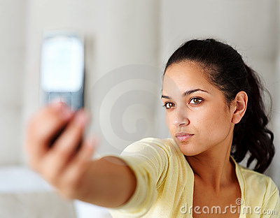 Young woman taking picture through mobile phone