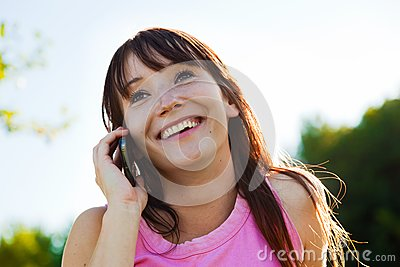 Young woman talking on mobile phone and smiling outdoors