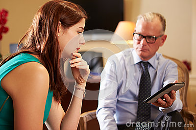 Young Woman Talking To Male Counsellor Using Digital Tablet