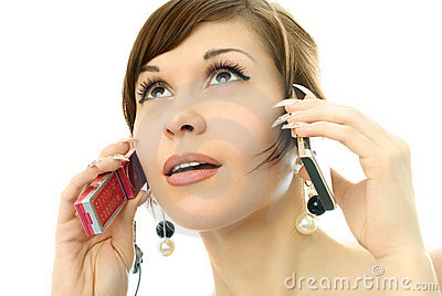 Young woman talking on two cell-phones