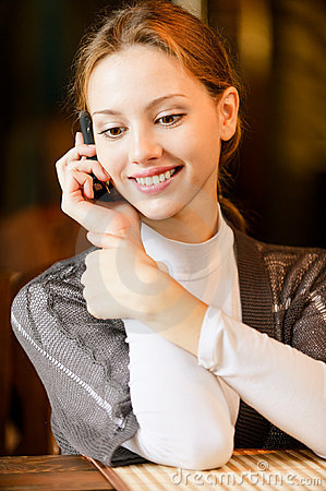 Young woman talks by phone.