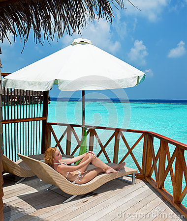 Young woman tans on a terrace .Maldives