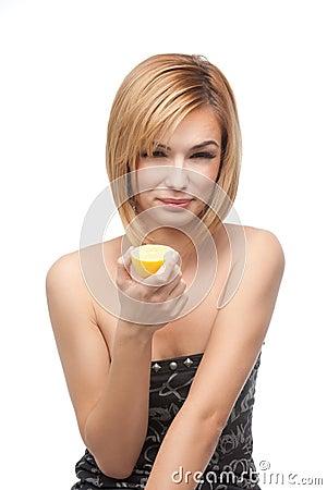 Young woman tasting a lemon