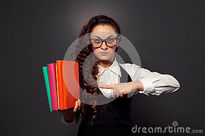 Young woman teacher in glasses pointing at pile of books
