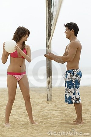 Young Woman Teasing Boyfriend with ball on Beach