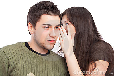 Young woman telling a secret to man