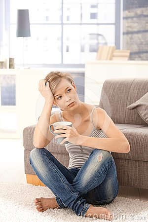 Young woman thinking with tea in hand