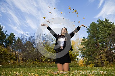Young woman throw autumnal leaves