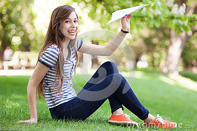 Young woman throwing paper plane