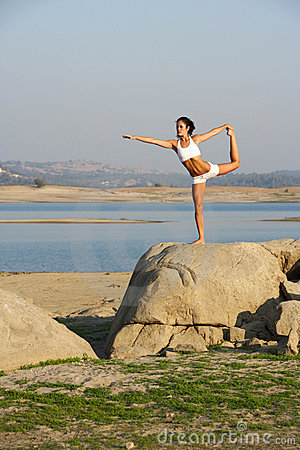 A young woman on top of a rock doing yoga
