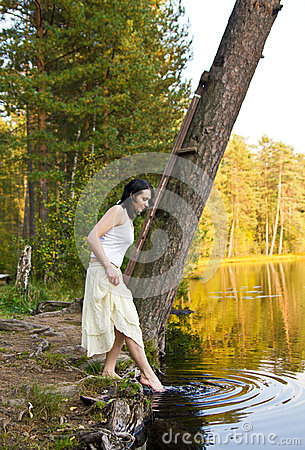 Young Woman touches water in the forest lake