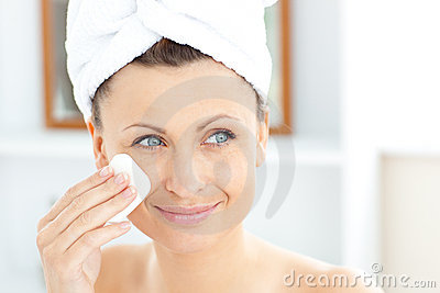 Young woman with a towel putting cream on her face