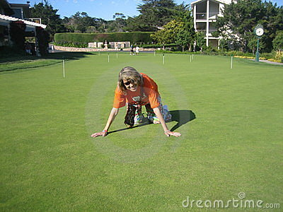 Young woman tries to dense lawn grass on the golf