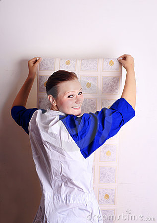 Young woman tries on wall-papers