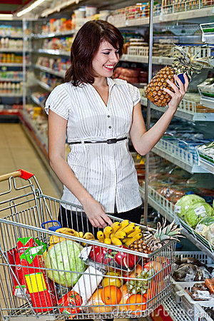 Young woman with a trolley at a supermarket