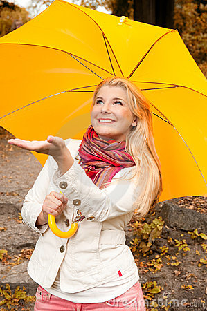 Young woman with umbrella in an autumn forest