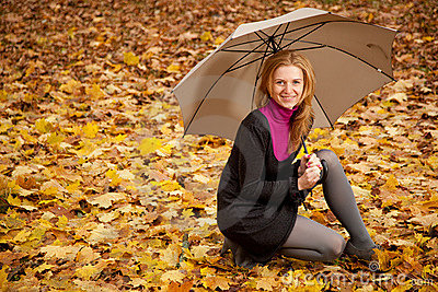 Young woman with umbrella with autumn leaves