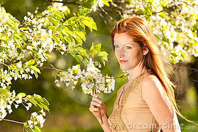 Young woman under blossom tree in spring