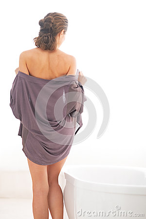 Young woman undressing in bathroom. rear view