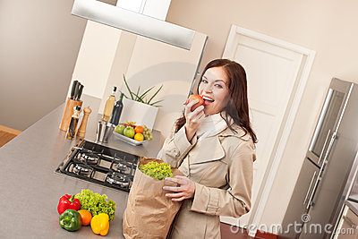 Young Woman Unpacking Shopping Bag In Kitchen Royalty Free Stock Images - Image: 13037439