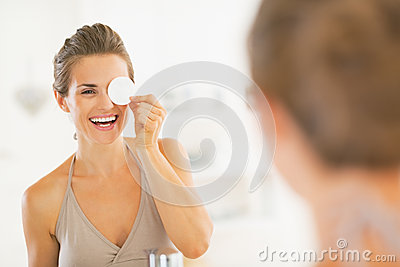 Young woman using with cotton pad in bathroom