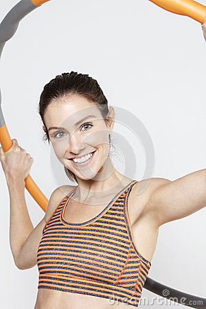 Young woman using a hula hoop, smiling Stock Photo