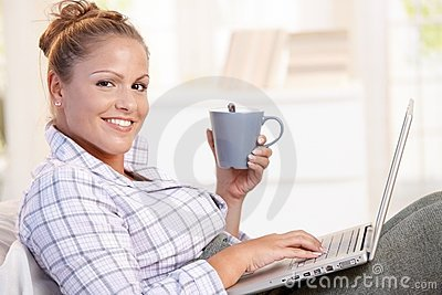 Young woman using laptop in bed drinking tea