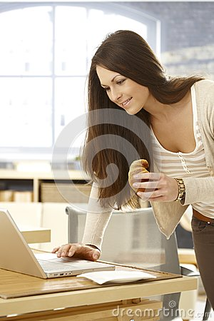 Young woman using laptop having croissant